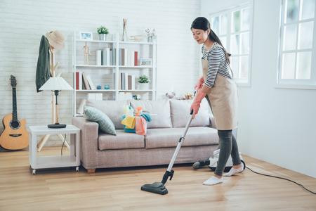 asiatische Dame, die Hausarbeit in der Schürze tut. Junge Hausfrau mit Staubsauger, die den Holzboden im Wohnzimmer säubert. glückliche Haushälterin, die zu Hause Hausarbeit mit attraktivem Lächeln im Gesicht macht. Standard-Bild