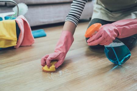 personas que hacen las tareas del hogar y el concepto de limpieza. Cerca de la mujer en guantes de goma con estropajo de limpieza de suelos de madera en casa. Señora rociando limpiador en el suelo de la sala de estar.