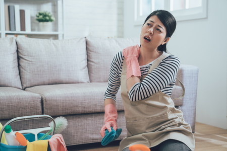 painful woman with shoulder hurts because of doing lots of house chores. young lady sitting on floor massage herself with a sick face holding blue rag with cleaning product in bucket nearby. Stock Photo