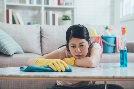 asian wife resting her head and arms on table in living room wants to take a nap. beautiful housewife doing housework in house. young lady feeling tired wiping table in the afternoon.