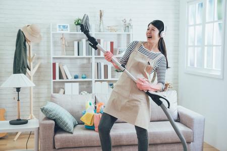 allegra moglie asiatica che indossa gli auricolari che suona l'aspirapolvere come una chitarra si gode la musica ballando mentre fa i lavori di casa nel soggiorno. giovane casalinga che fa gioiosamente le faccende domestiche a casa.
