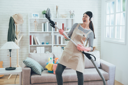 cheerful asian wife wearing earphones playing vacuum cleaner as a guitar enjoy music dancing while doing housework in the living room. young housewife joyfully doing house chores at home.