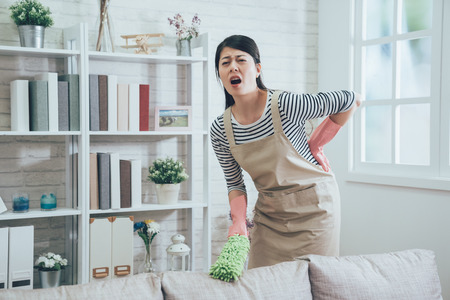 housewife wearing apron with a painful face putting hands on her waist. wife in rubber protective gloves hurts her body  while cleaning the house. young woman doing housework at home.