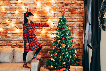 adorable girl kid in reindeer decorating christmas tree with baubles at home. little child standing high on sofa holding golden ball. lights hanging on red brick wall in background.