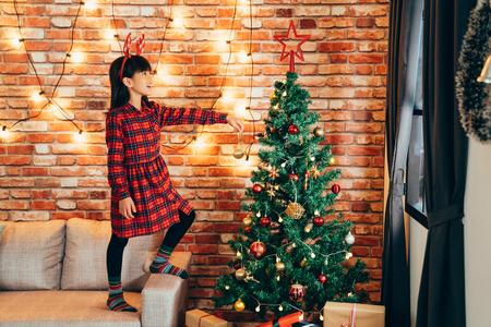 entzückendes Mädchenkind in Rentieren, das zu Hause den Weihnachtsbaum mit Kugeln schmückt. kleines Kind, das hoch auf dem Sofa steht und goldene Kugel hält. Lichter hängen an der roten Backsteinmauer im Hintergrund.