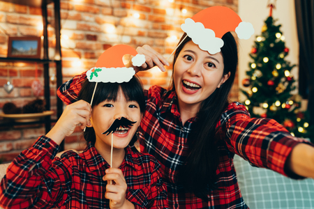 sweet family having fun playing with paper decoration making funny face taking selfie at home celebrating christmas eve. cute santa girls enjoy cheerfully spending time together on holiday.