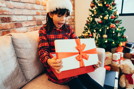little cute girl open christmas gift box with a surprised face. cheerful kid excited looking at xmas present. decorated room with tree and teddy bear for coming up holidays winter vacation new year. Stock Photo