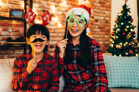 happy family having fun playing with paper decoration on sofa with decorated christmas tree in background. young mom with santa hat and xmas glasses. little kid playing funny mustache with reindeer.
