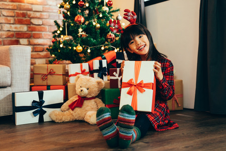 cute daughter face camera showing big gift box enjoy smiling sitting on ground near decorated Christmas tree and teddy bear. attractive girl childhood with reindeer got xmas present from santa claus. Stock Photo