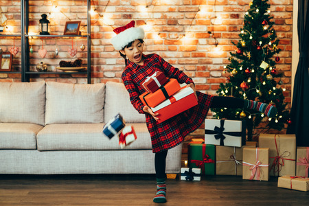 happy little girl holding many christmas gifts falling down on floor indoor decorated living room. lovely kid wearing santa hats sending presents to family on xmas eve. colorful boxes under tree home