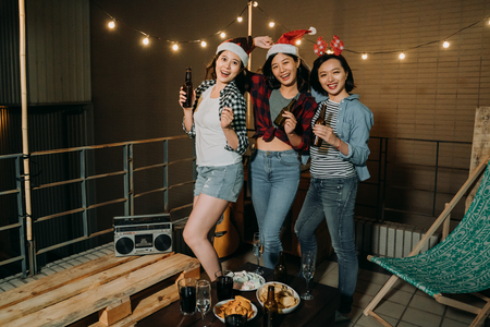Dakfeest met een groep beste vrienden. drie jonge vrolijke mensen dansen en bier drinken op het dak van het gebouw. gelukkige zorgeloze aziatische vrouwen genieten 's nachts van muziek op het balkon.