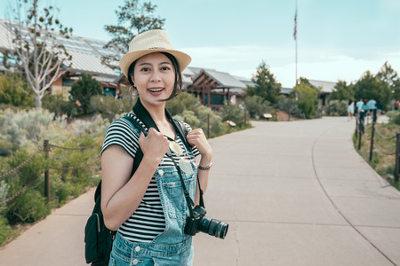 young traveler walking into the grand canyon south rim hotels. lady photographer decided to stay at the resort in the trip. elegant lens man face camera smile attractive. Reklamní fotografie