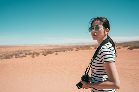 Nature Photographer taking pictures outdoors during hiking trip on grand canyon national park. young lady travel alone to the sand mountain in usa. female with sunglasses standing on desert sunny day