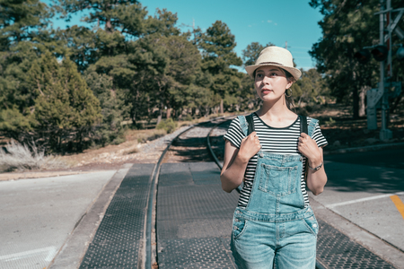 young lady traveler walking on the railway on sunny day by the forest. female tourist self guided trip in usa. asian backpacker wearing straw hat travel wild on summer vacation. Stock fotó