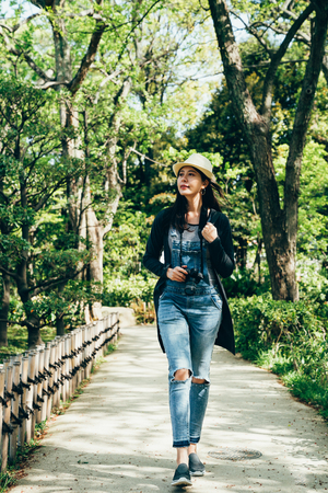 young woman backpacker walking in japanese garden. full length of girl photographer breathing fresh air in green forest  . path with beautiful nature trees around.