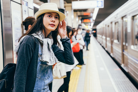 lady tourist curiously looking around waiting train on platform . subway arrived the railway station. people standing beside the metro ready to get in. Stock Photo