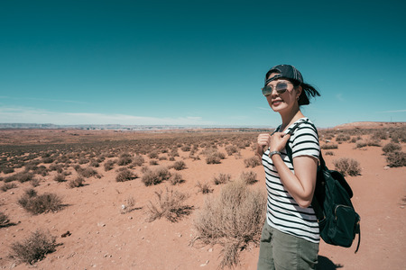 travel lifestyle backpacker walking in the hot sand ground with sunglasses. young girl love visit wild nature freedom in summer. Female hiking woman happy and smiling during hike trek.