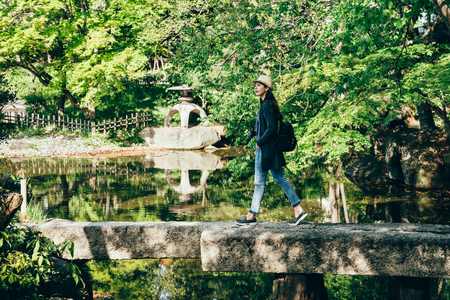 full length of young girl lens man enjoying walking in beautiful amazing nihon teien. cheerful traveler walking on stone bridge through the pond with clean water.
