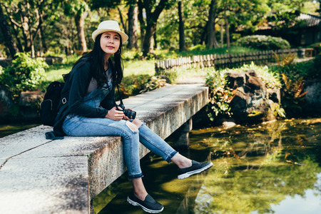 young woman traveler relaxing in japanese garden. girl photographer sitting on the stone bridge road above the pond with green water. elegant lady enjoy the view in the forest on sunny day.