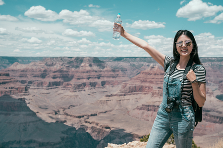 carefree young lady traveler relaxing standing on the top of skyline on summer vacation. woman hiker happy showing bottler water raising hands on grand canyon national park. female tourist joy trip. Stockfoto