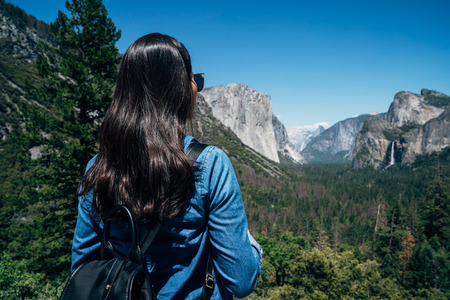 woman hiker looking at view hiking in mountain in yosemite national park. young asian backpacker in nature landscape trekking wearing backpacks. girl enjoy amazing forest nature view summer vacation 版權商用圖片