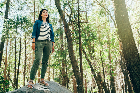 full length young girl hiker love wild lifestyle travel in forest on sunny day. asian backpacker standing high on the big rock wearing sandals. outdoor trip in yosemite national park California usa. 版權商用圖片