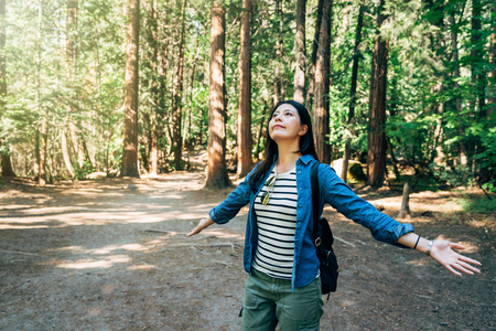 Carefree cheering woman in spring or summer forest park full of hope and vitality. girl hiker raising her arms up smiling happy enjoy fresh air. young asian backpacker yosemite national park travel. Stock fotó