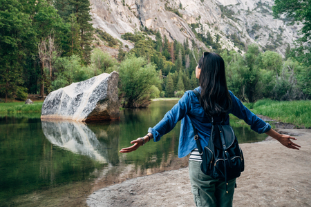 back view of freedom woman opening arms hugging nature. carefree girl traveler enjoy love wild sightseeing relaxing near by mirror lake in yosemite national park. young asian travel holiday on summer