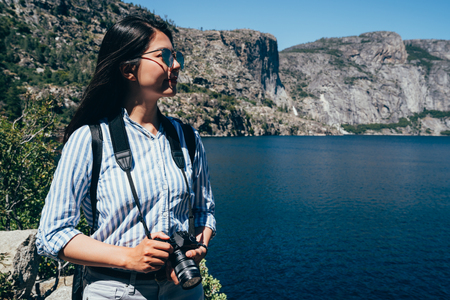Asian Chinese lady photographer with sunglasses tour trip in hetch hetchy reservoir. young girl hiker travel in yosemite national park in san franisco holding camera. sightseeing the nature usa.
