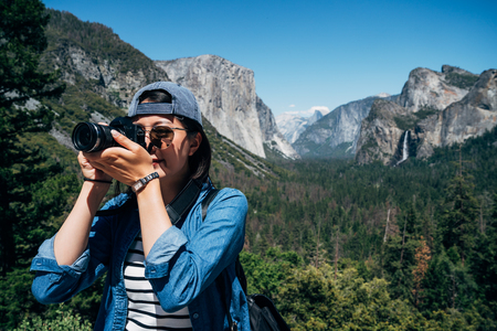 Nature female Photographer taking pictures outdoors during hiking trip in yosemite national park. young asian girl love photography travel nature california on sunny day. woman zooming taking photo. Stok Fotoğraf