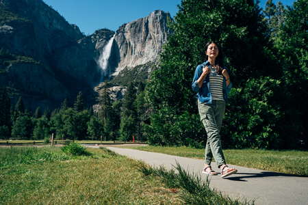 full length of young asian backpacker walking on path wearing sandals hiking in yosemite national park on sunny day in summer vacation trip usa. amazing bridalveil fall in background with blue sky.