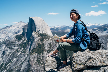 cool female backpacker sitting on the big rock on top of mountain in yosemite national park. young asian hiker holding paper map checking the destination in hiking travel. woman backpacker enjoy view Stock Photo