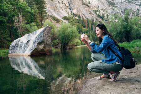 asian travel woman kneeling down holding mobile phone taking picture of amazing nature view mirror lake in yosemite national park us. young girl hiker with backpack love wild travel trip in forest.