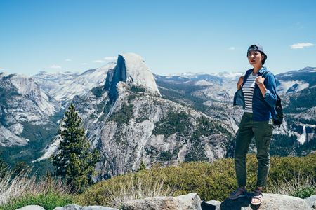 full length of healthy hiker girl standing relaxing sightseeing in nature hike half dome in background. Beautiful young woman hiking happy with cap travel in Yosemite National Park California USA.