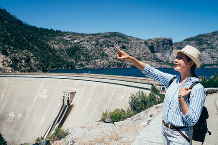 young girl backpacker visit OShaughnessy Dam at Hetch Hetchy Reservoir. Asian woman pointing to the blue sky with joyfully smile on face. lady with straw hat standing in nature in usa.