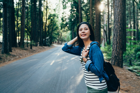summer nature getaway road trip happy camper Asian girl on camping travel holidays during hot season in yosemite national park usa. young asian hiker standing on the road looking smiling while sunset