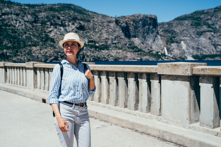 Hiker portrait of female hiking woman happy and smiling during hike trek on hetch hetchy reservior. Beautiful young Asian Chinese lady walking on the stone bridge surrounding the mountains. 版權商用圖片