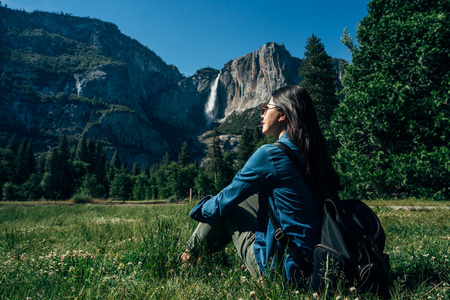 girl hiker relaxing sitting on green grass enjoy sunshine and beautiful mountain nature view in yosemite national park. young woman wearing sunglasses resting having self guided trip in usa.