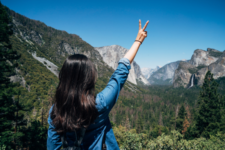 back view of young female backpacker raising hands with victory finger sign. carefree woman hiker enjoy nature in the mountain yosemite national park california america. beautiful view under blue sky