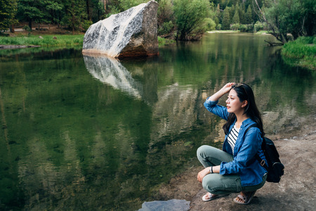 Nature banner woman kneeling down relaxing at mirror lake view of Summer Palace in yosemite national park. Asian girl travel in usa love wild nature lifestyle concept. female backpacker in sunglasses
