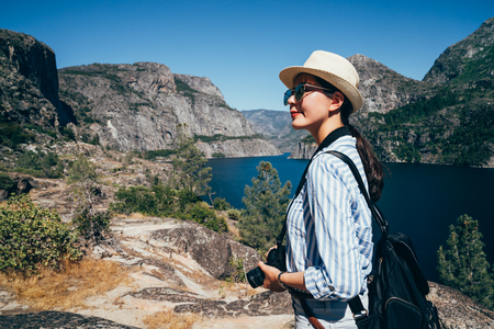 Asian lady tour trip in hetch hetchy reservoir. young backpacker wearing straw hat sightseeing beautiful nature view of o shaughnessy dam. young chinese woman standing outdoor surrounding mountain