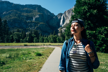 hiker woman in hat walking in path in forest with high mountain in background in yosemite national park. confident female traveler enjoy wild nature lifestyle concept in summer. asian travel usa.