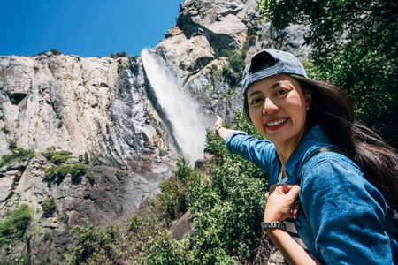 woman hiker cheerfully face camera showing amazing nature attraction waterfall in yosemite national park. young girl hiking trip travel in California usa. beautiful lady with hat smiling attractive. 版權商用圖片