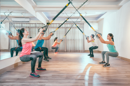 group of young asian people doing squat with fitness suspension straps. healthy sporty friends working out in a sunny bright gym. five students in training lesson concentrated doing exercise.