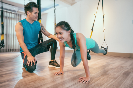 asian woman performing total body resistance exercise training in gym with personal coach. Sporty girl doing kicking legs exercise with elastic rope. sportswoman works out at health club. Banque d'images - 113314421