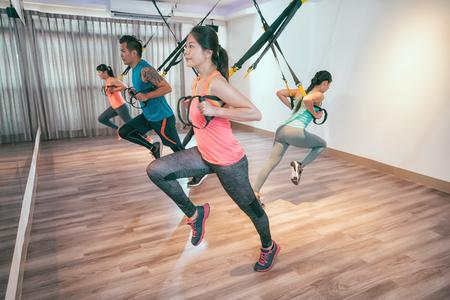 jóvenes asiáticos que hacen ejercicios de cuerda elástica en la sala de crossfit tirando con toda la fuerza del cuerpo. Grupo de amigos felices trabajando juntos en el gimnasio tomando una lección de ejercicio de resistencia corporal total. Foto de archivo