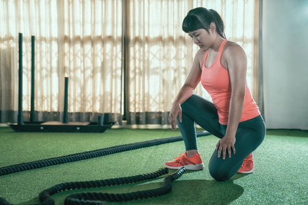 female athlete looking at battle rope on green floor ready to training stronger arms muscle in gym. young asian muscular trainer kneeling down to tidy at the classroom after sport lesson in club Stock Photo
