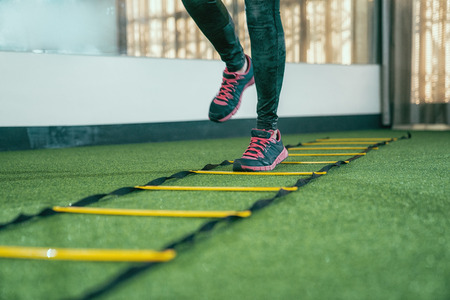 unrecognized female athlete practicing for hurdle running race in gym. focus on legs with sneakers doing workout run faster quicker in a health club. people love sports exercise lifestyle concept.
