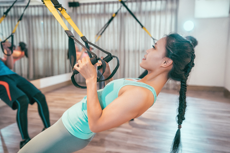 People at gym doing elastic rope exercises at crossfit room. group of young asian using trx straps training body stronger. happy beautiful woman doing sports loves bodybuilding lifestyle concept.