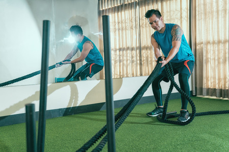 tired muscular male trainer pulling the heavy battle rope to tidy up the room at health club. young coach holding battling ropes in sport gym. handsome asian with sportswear and tattoo on arms.